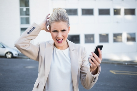 Furious stylish businesswoman holding her phone outdoors on urban background Stock Photo - 22302156