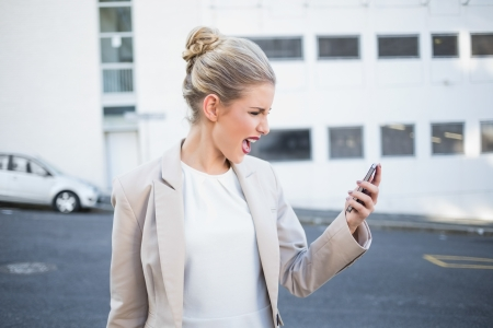 Furious stylish businesswoman shouting at her phone outdoors on urban background Stock Photo
