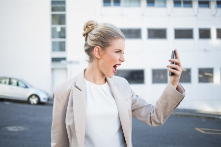 Angry stylish businesswoman shouting at her phone outdoors on urban background photo