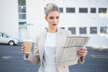 unsmiling: Stern stylish businesswoman reading newspaper outdoors on urban background
