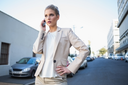 Serious elegant businesswoman on the phone outdoors on urban background Stock Photo - 22302175