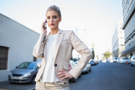 Stern elegant businesswoman on the phone outdoors on urban background Stock Photo - 22302176