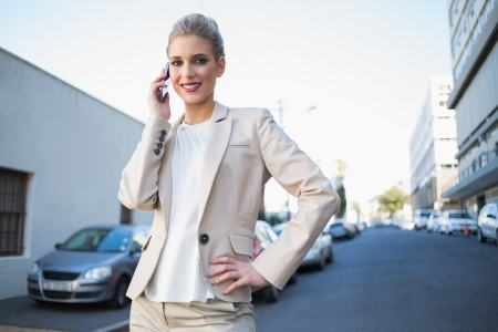 Cheerful elegant businesswoman on the phone outdoors on urban background Stock Photo - 22302177