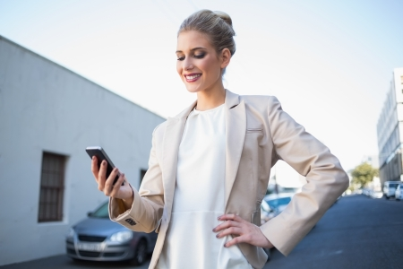 Smiling elegant businesswoman looking at her smartphone outdoors on urban background Stock Photo - 22302179
