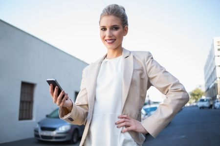 Cheerful elegant businesswoman holding smartphone outdoors on urban background Stock Photo - 22302180