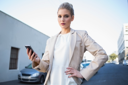 Stern elegant businesswoman holding smartphone outdoors on urban background Stock Photo - 22302181