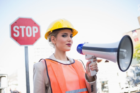 Serious businesswoman wearing builders clothes holding megaphone outdoors on urban background Stock Photo