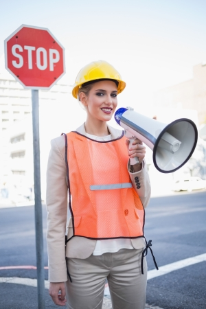 Smiling businesswoman wearing builders clothes shouting in megaphone outdoors on urban background photo