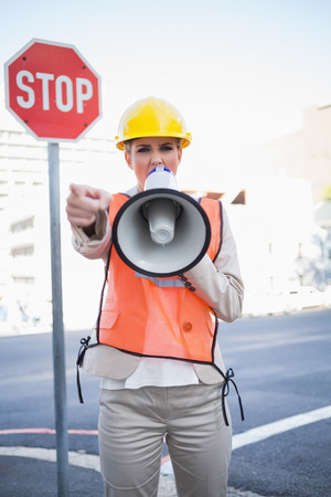 Businesswoman wearing builders clothes screaming in megaphone outdoors on urban background photo