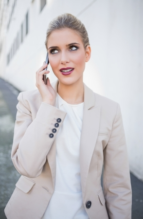Smiling attractive businesswoman on the phone outdoors on urban background Stock Photo - 22341418