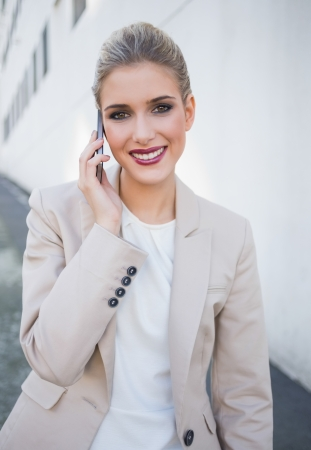 Cheerful attractive businesswoman on the phone outdoors on urban background Stock Photo - 22302207