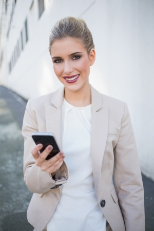 Smiling attractive businesswoman sending a text outdoors on urban background Stock Photo - 22341420