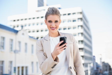 Happy attractive businesswoman sending a text message outdoors on urban background