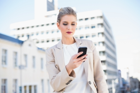 Peaceful attractive businesswoman sending a text message outdoors on urban background photo