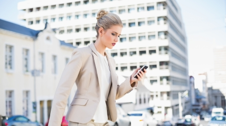 Focused gorgeous businesswoman text messaging outdoors on urban background photo