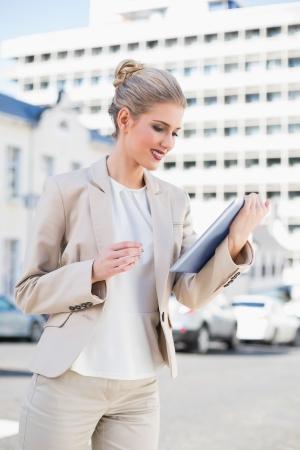 mujer elegante: Sonrisa hermosa empresaria utilizando tablet pc al aire libre en medio urbano