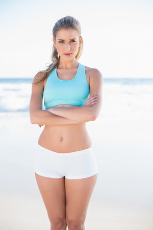 Serious sporty blonde in sportswear posing on a sunny beach photo