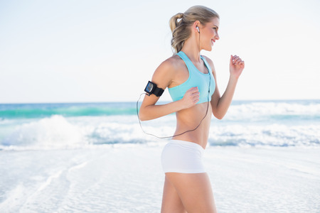 Smiling sporty blonde in sportswear jogging on a sunny beach Stock Photo