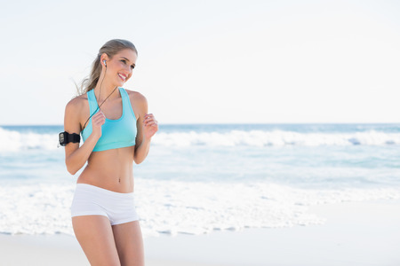 Smiling sporty blonde in sportswear running on a sunny beach photo