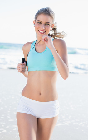 Cheerful sporty blonde in sportswear jogging on a sunny beach