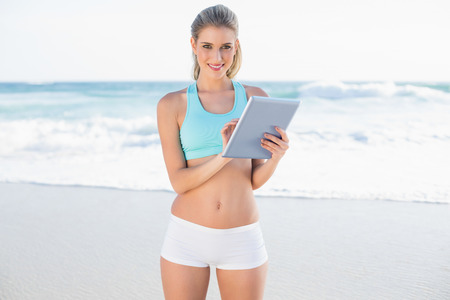 Smiling slender blonde in sportswear using tablet on a sunny beach photo