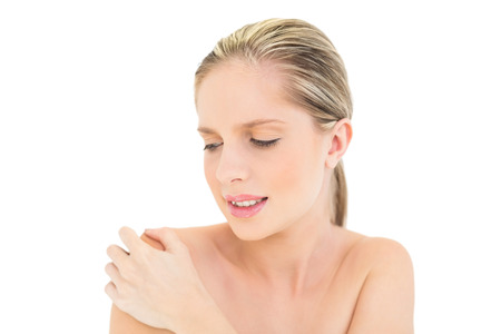 Irritated fresh blonde woman looking at her shoulder on white