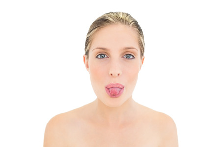 silliness: Charming fresh blonde woman posing with tongue out on white background