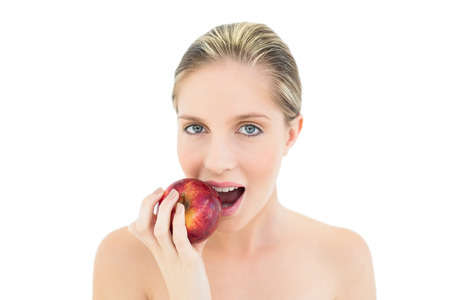 Beautiful fresh blonde woman eating a red apple on white  photo