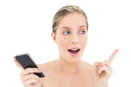 cut out device: Shocked fresh blonde woman holding a mobile phone and raising her finger on white  Stock Photo