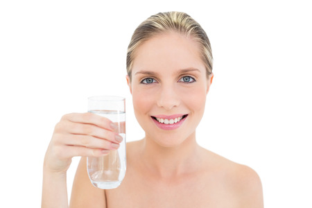 Amused fresh blonde woman holding a glass of water on white