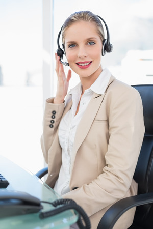 Peaceful blonde call centre agent posing in bright office photo