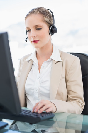 Peaceful blonde call centre agent working on computer in bright office photo