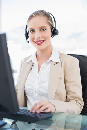 Cheerful blonde call centre agent working on computer in bright office photo