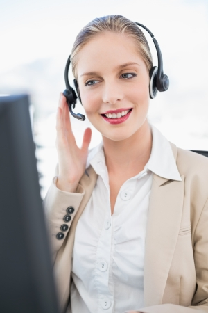 Content blonde call centre agent interacting with customer in bright office photo