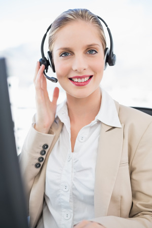 Smiling blonde call centre agent interacting with customer in bright office photo