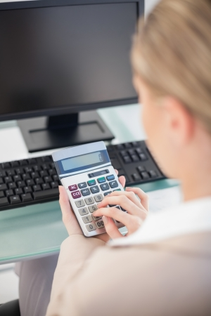 over the shoulder view: Over shoulder view of businesswoman using calculator in bright office