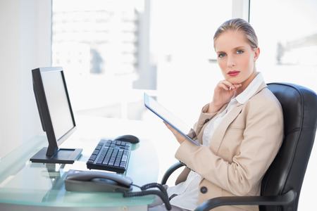 Thoughtful blonde businesswoman in bright office using tablet photo
