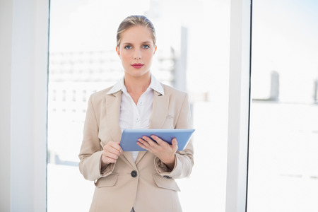 Serious blonde businesswoman using tablet pc in bright office photo