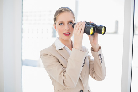 Peaceful blonde businesswoman in bright office holding binoculars photo