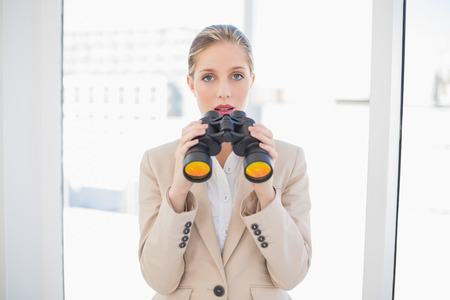 Astonished blonde businesswoman in bright office holding binoculars photo