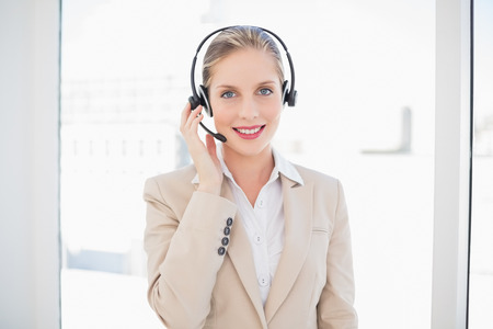 Smiling blonde call centre agent standing in bright office photo