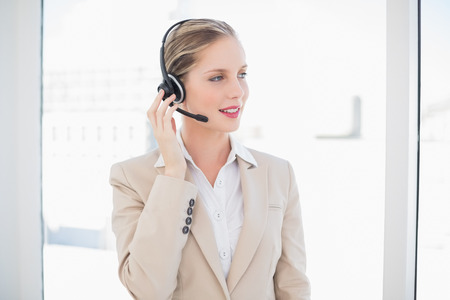Cheerful blonde call centre agent standing in bright office photo