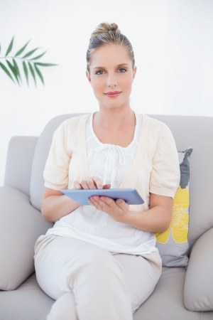 Peaceful fresh model in white clothes using tablet pc sitting on cosy sofa photo