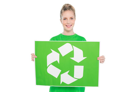 activist: Smiling blonde environmental activist holding recycling sign on white