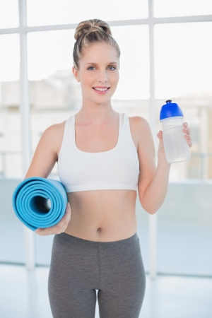 Smiling sporty blonde holding flask and exercise mat in bright room photo