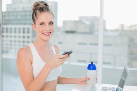 Smiling athletic blonde in bright room sending a text  photo