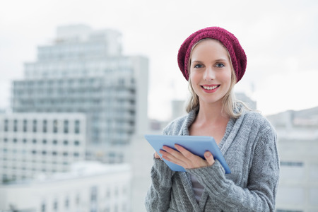 Smiling pretty blonde using tablet pc outdoors  photo