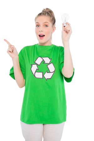 Surprised environmental activist wearing recycling tshirt holding light bulb on white background photo
