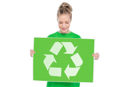 Content blonde environmental activist holding recycling sign on white background photo