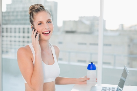 Laughing sporty blonde on the phone in bright room photo